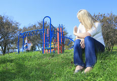 Mother look at boyfriend and children play on the. A mother look at boyfriend and children play on the playground Royalty Free Stock Photography