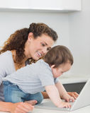 Mother looking at baby boy using laptop Royalty Free Stock Image