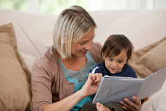 Mother looking at a book with her son Stock Photos