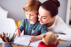 Mother looking at child drawing a picture Stock Image