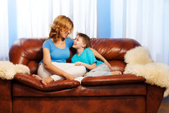 Mother is looking at child sitting on couch Stock Photo