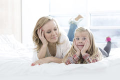 Mother looking at cute daughter making faces while lying in bed Stock Photo