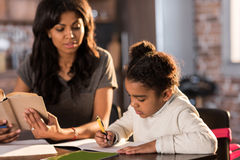 Mother looking at cute little daughter doing homework at home Royalty Free Stock Image