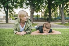 mother looking at cute son lying on green grass royalty free stock image