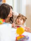 Mother Looking At Daughter Eating Cupcake Royalty Free Stock Image