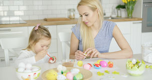 Mother looking at girl coloring eggs Royalty Free Stock Images