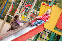 Mother looking at her daughter on slide Royalty Free Stock Photography