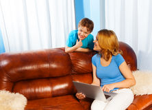 Mother looking at her son on sofa with laptop Stock Photo