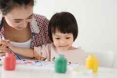 Mother looking how her child daughter drawing a picture.  stock images