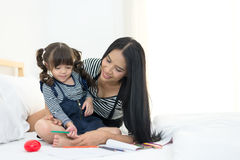 Mother looking how her child daughter drawing a picture. On the bed stock photography