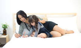 Mother looking how her child daughter drawing. A picture on the bed stock image