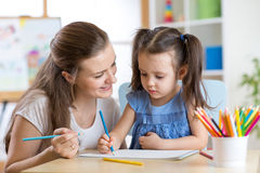 Mother looking how her child daughter drawing a picture. Young mother looking how her child daughter drawing a picture stock image