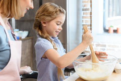 Mother looking at little daughter preparing dough in glass bowl Stock Photos