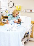 Mother Looking At Newborn Baby While Sitting In Stock Photography