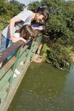 Mother Looking into Pond with Two Daughters Stock Photography