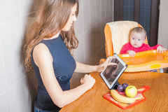 Mother looking for recipe of preparation of baby food Royalty Free Stock Photos