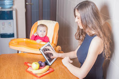 Mother looking for recipe of preparation of baby food Stock Images