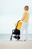 Mother looking through the sea while walking with stroller Stock Photo
