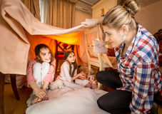 Mother looking at two girls playing at bedroom in house made of Stock Photo