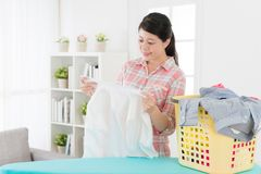 Mother looking at white shirt feeling satisfaction. Happy smiling mother looking at white shirt feeling satisfaction when her family clothing getting clean from Royalty Free Stock Photo