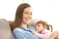 Mother looking at you with her daughter sleeping. Over her chest sitting on a couch at home Stock Photo