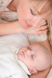 Mother looks at sleeping baby boy Royalty Free Stock Photos