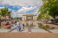 Mother looks at her son who is playing in water at a square in front of an historical city gate in Amsterdam. AMSTERDAM, THE NETHERLANDS - AUG 14, 2016 : People royalty free stock images