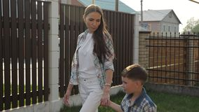 Mother with loose dark hair holds adorable little boy hand. Beautiful mother with loose dark hair holds adorable little son hand walk speaking in green yard stock video footage