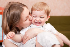 Mother love. Young mother is kissing her little son Royalty Free Stock Images