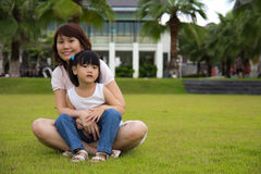 Mother love. Lovely mother hugs her daughter, both sit on a green field Stock Photography