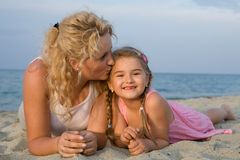Mother love. Mother kissing her little daughter at the beach while having summer holiday stock photography