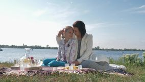 Mother love, happy young mama with child girl hugging during relaxation on family picnic on meadow stock video