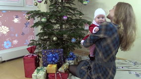 Mother with lovely baby girl on her hands have fun near fir tree stock video
