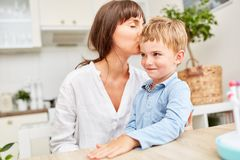 Mother lovingly kisses her son`s forehead. Happy mother lovingly kisses her son on the forehead in the kitchen Stock Photography