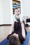 Mother lying on back and holding her baby during a yoga class Royalty Free Stock Images