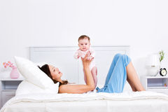 Mother lying on the bed and playing with baby stock photo