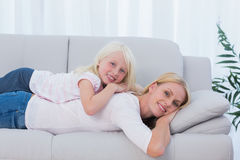 Mother lying on couch with her daughter on her back Royalty Free Stock Image