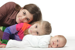 Mother lying on the floor with her kids Stock Images