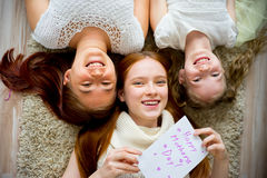 Mother lying on floor with her two daughters Stock Photo