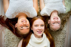 Mother lying on floor with her two daughters Stock Images