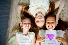 Mother lying on floor with her two daughters Royalty Free Stock Image