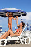 Mother lying on lounger. daughter standing near. Young mother lying on lounger under beach umbrella. little daughter in bathing suit standing near mother and Stock Photo