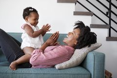 Mother Lying On Sofa At Home Playing Clapping Game With Baby Daughter royalty free stock image
