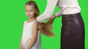 Mother makes daughter hairstyle on a green screen, chroma key stock footage
