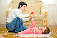 Mother makes daughter massage Stock Images
