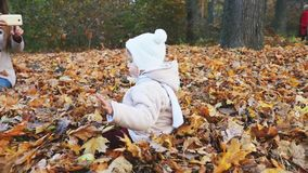 Mother makes footage of baby at autumn park, mobile phone