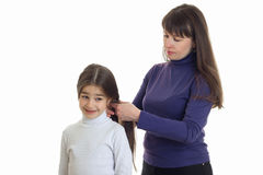 Mother makes a hairstyle to her little daughter Stock Photography