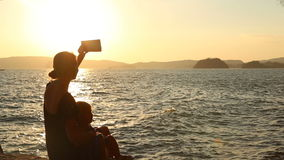 Mother makes selfy  with daughter against backlight at sunset. Young blonde mother makes selfy with little daughter against backlight at background of island at stock video footage