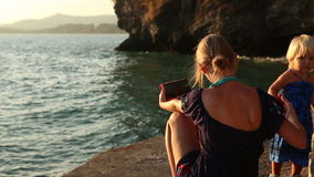 Mother makes selfy near daughter against cliff at sunset stock video footage