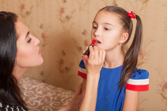 Mother makes up lips of her little daughter Stock Photo